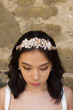 Load image into Gallery viewer, Black haired model wears a pale rose gold and pearl low bridal headband with a stone wall behind