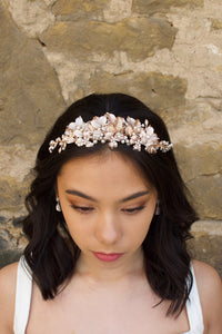 Black haired model wears a pale rose gold and pearl low bridal headband with a stone wall behind
