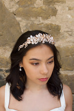 Load image into Gallery viewer, Black haired model wears a pale rose gold and pearl low bridal headband with stone background