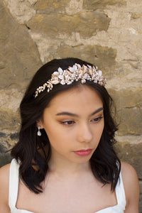 Black haired model wears a pale rose gold and pearl low bridal headband with stone background