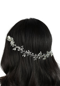 single row of crystals on a silver wire worn on dark hair with a white background
