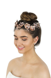 Brown hair model wears a rose gold headpiece on her forehead against a white background