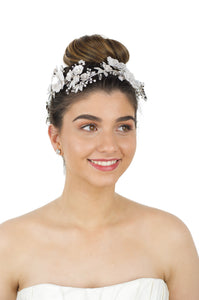 Model with light brown hair wearing a white headpiece against a white background
