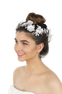 Brown hair model wears a white flower vine on her forehead against a white background
