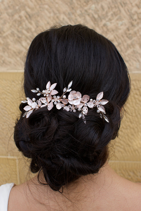 A Pale Rose Gold comb sits at the back of a dark haired Bride
