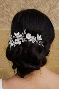 A Pale Silver Hair piece with leaves and flowers sits at the back of a dark hair bride