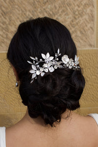 A white Silver Comb with flowers and pearls sits at the back of a dark hair bridal model