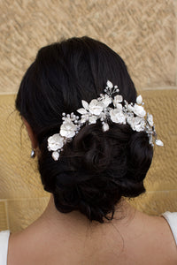 Bride wears Soft Silver Flowers Bridal Comb in her dark hair with a stone wall background