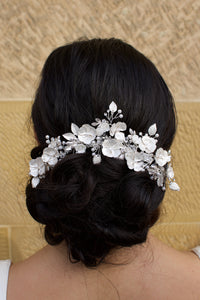 Silver flowers and leaves bridal hair piece with a white look worn by a curly haired model with a stone wall background.