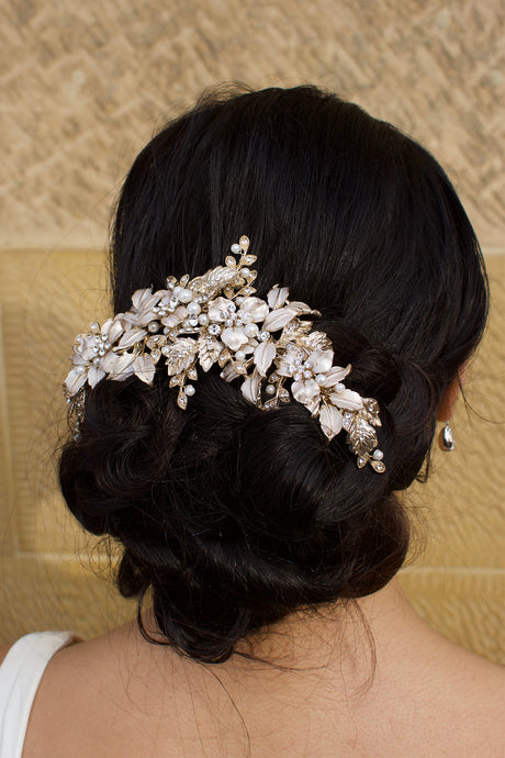 A wide Bridal Headpiece of gold leaves at the back of a model's head with a stone wall backdrop