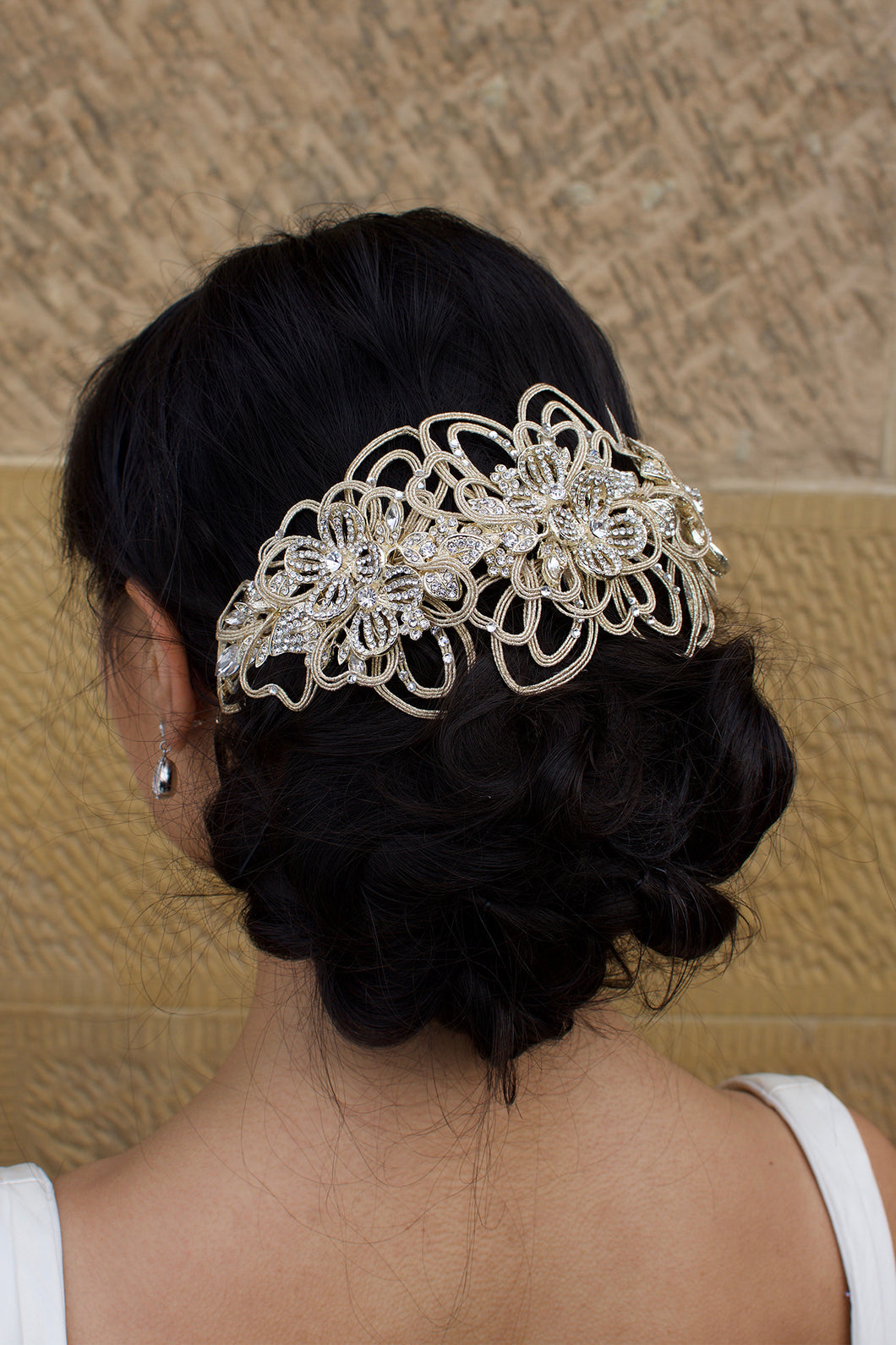 Bride with black hair wears a matt gold wide headpiece on the back of her head with a stone wall behind