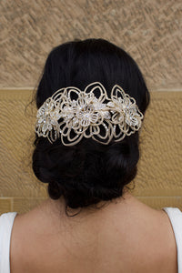 Bride wears a matt gold bridal comb on her dark hair in front of a stone wall