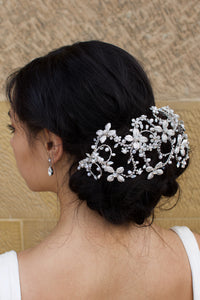 Dark hair model wears a Silver Bridal Headpiece over a large bun of hair with a stone wall background