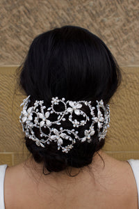 A black hair bridal model wears a wide silver hair cage on a bun of hair. There is a stone wall background