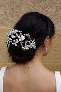 Looking right a Bridal Model wears a silver wide headband on her dark hair with a stone wall background