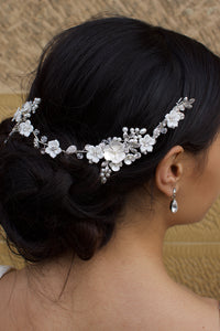 Silver and white flower bridal vine worn on a dark hair model