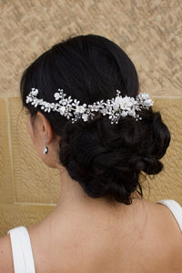 A black haired Bride wears a porcelain flowers silver vine around the back of her head with a stone wall backdrop