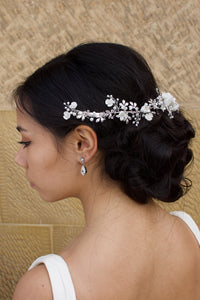 A dark haired Bride wears a porcelain flowers silver vine around the back of her head with a stone wall backdrop