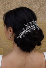Load image into Gallery viewer, Black Hair Bride wearing a Silver Crystal vine around the back of her hairstyle with a stone wall background