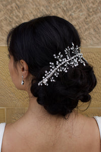 Black Hair Bride wearing a Silver Crystal vine around the back of her hairstyle with a stone wall background