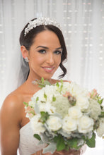 Load image into Gallery viewer, Bride with bouquet of flowers wearing a silver leaf crown  and a curl of hair down one side