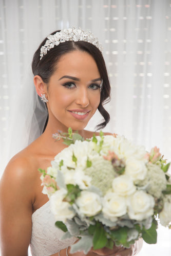 Bride with bouquet of flowers wearing a silver leaf crown  and a curl of hair down one side