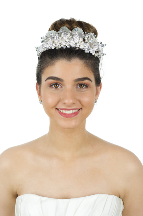 A black haired model wears a Bright Silver tiara with pearls in the background is White
