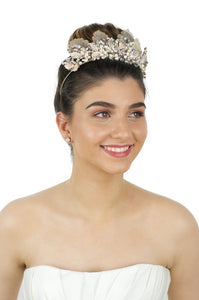 A black haired model wears a gold tiara with pearls on bright White background.