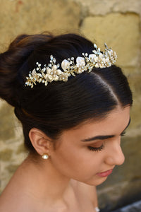 A side view of a model wearing a gold flowers headband on her dark hair with an old stone wall background