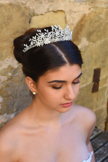A silver crystal bridal tiara worn by a dark haired model in front of a stone wall