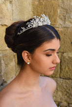 Load image into Gallery viewer, A side view of a silver crystal tiara worn by a dark haired model in front of a stone wall