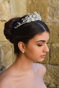 A side view of a silver crystal tiara worn by a dark haired model in front of a stone wall