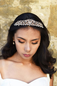 Dark hair model wears a crystal tiara at the front of her head. The backdrop is an old stone wall