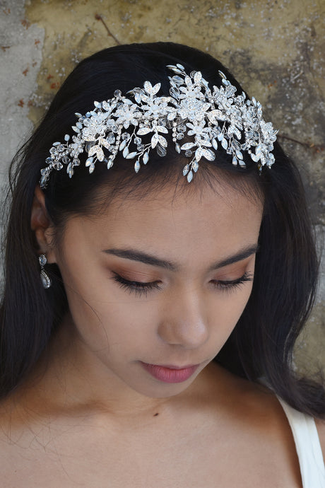 Wide headband in silver with white opal stones worn by a dark haired bride