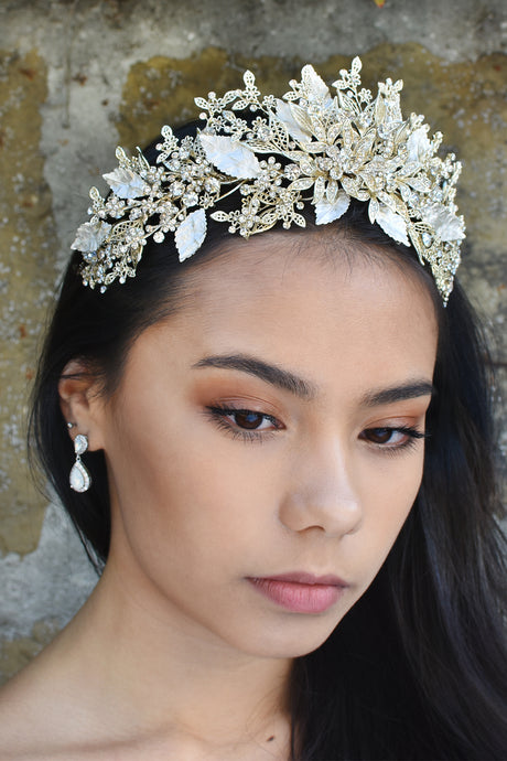 High Tiara of pale gold leaves and swirls worn by a dark haired model with a white opal earring