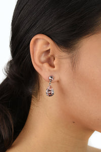 Black hair bride wears a pear shape earring in silver with an vintage rose stone