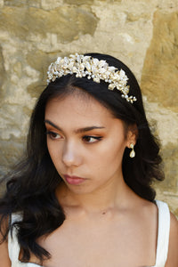 Dark hair bride wears a very pale gold tiara with pearls with a pear shape earring and a wall as background