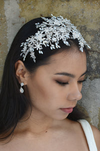 Silver wide headband with white opal stones worn by a model bride