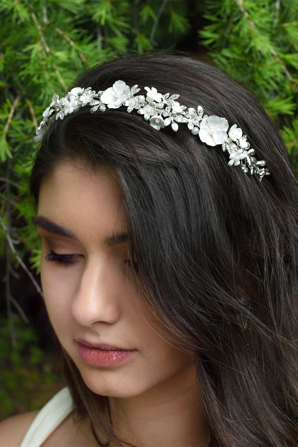 Dark hair model wearing a silver and flowers bridal headband with a pine tree bsckground
