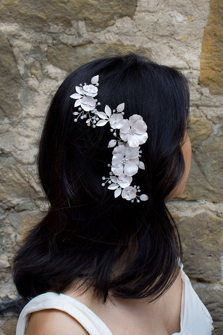 Black haired model wears a white bridal comb in front of a stone wall