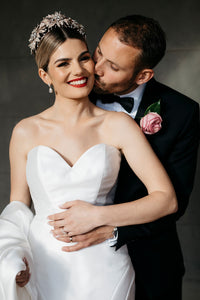 A beautiful real bride wearing a rose gold flower tiara being kissed by her new husband