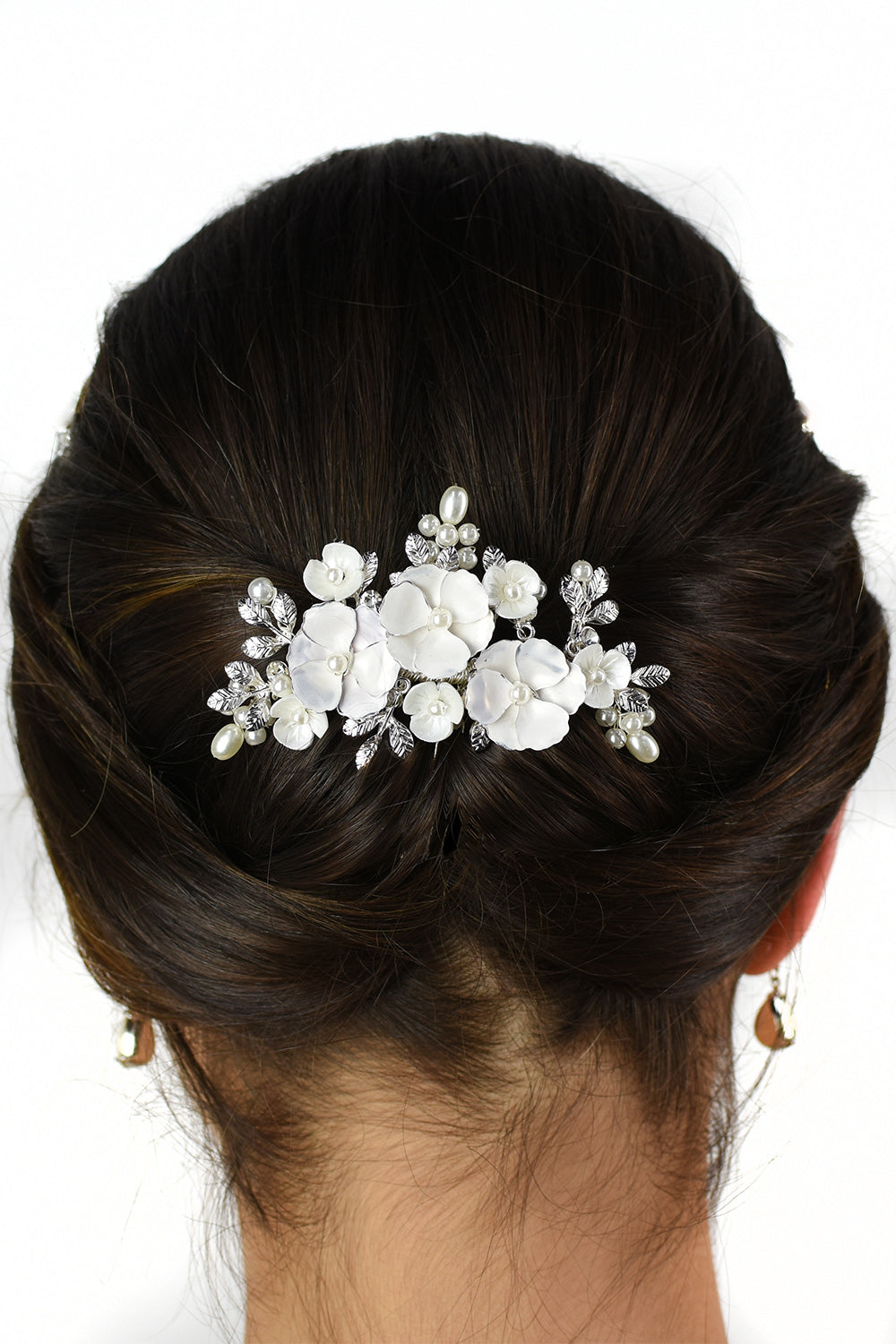 The back of a models' head with her brown hair wearing a white flower comb