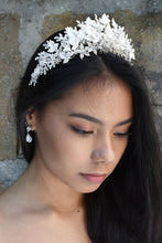Load image into Gallery viewer, A model looks down with dark hair wearing a soft silver tiara made of leaves.
