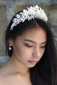 A model looks down with dark hair wearing a soft silver tiara made of leaves.