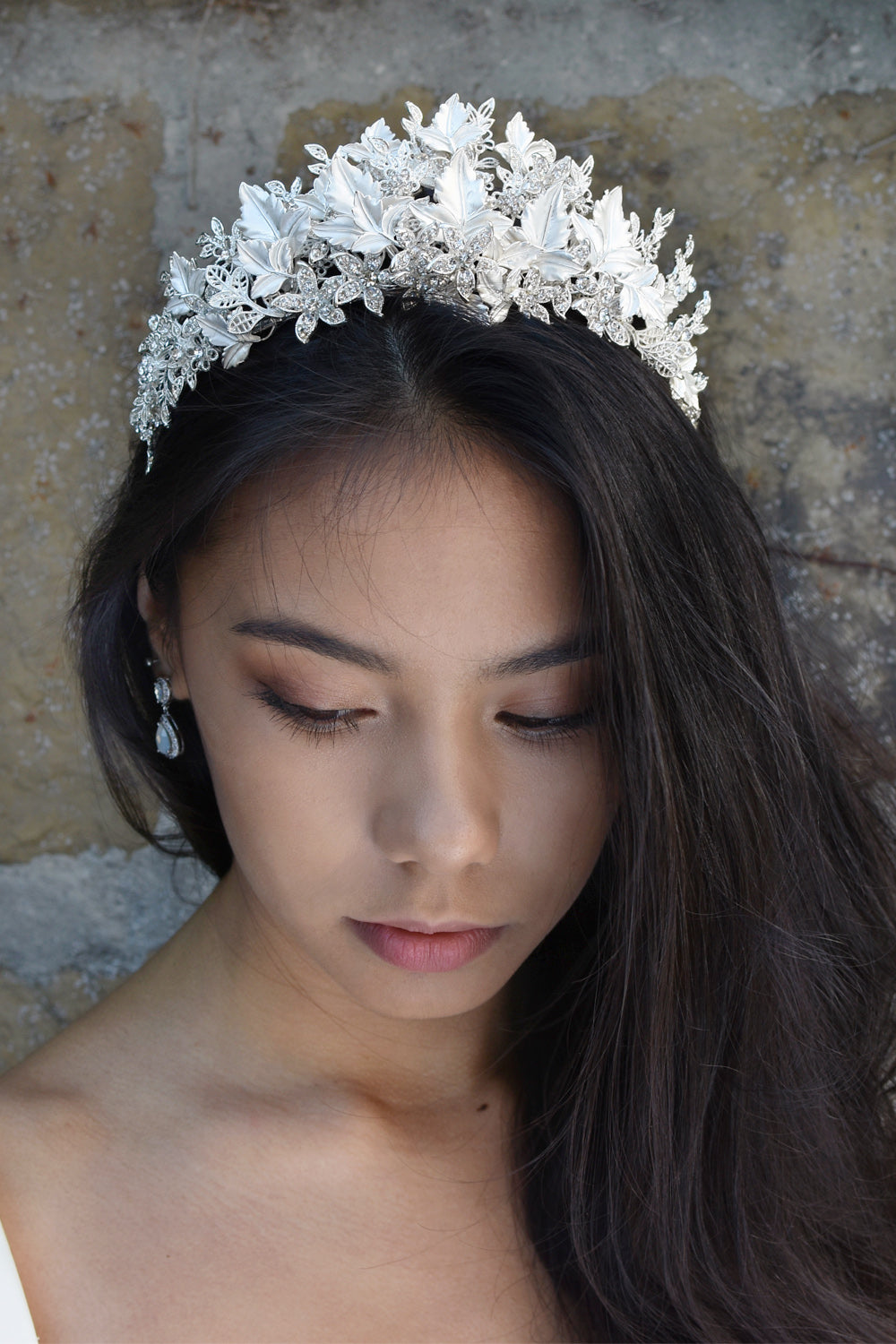 A black haired model wears a Bridal Crown of Silver leaves with a background of a stone wall