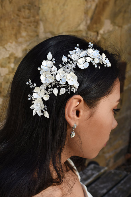 A Dark haired model wears a long side comb with flowers and a small earring