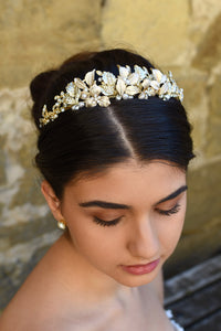 Black haired model wears a pale gold and pearl low bridal headband
