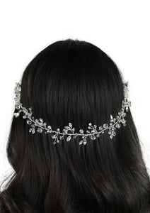 Black hair model has a single strand of wire with  crystals attached. Photo on a white background