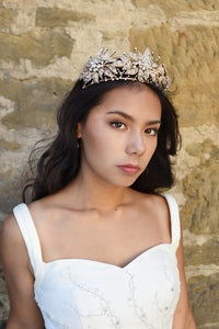 A handmade rose gold flower crown worn by a dark haired model side view