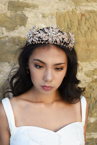 A handmade rose gold flower crown worn by a dark haired model